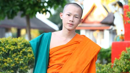 šafrán : LUANG PRABANG, LAOS - DECEMBER 9, 2016:Video portrait of a young Buddhist monk. Monks are educated in Buddhist schools at the citys temples