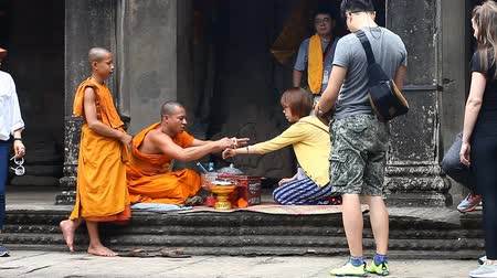 mantra : Siam Reap Angkor Wat, Cambodia - January 12, 2017:Cambodian buddhist monk reading mantra for tourist.Tourists and pilgrims leave donations for the preservation and restoration of complex Angkor Wat