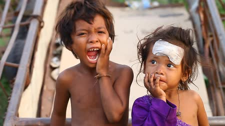 gerek : Siam Reap, Cambodia - January 14, 2017: A homeless boy with his young sister living in a house from empty boxes and construction debris.