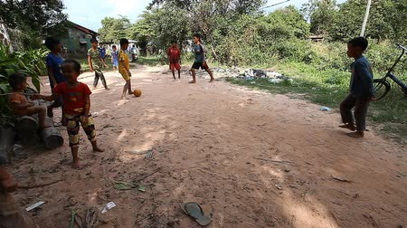 külvárosok : Siam Reap, Cambodia - January 13, 2017: Cambodian children play football on the road in their poor village . Living in poor settlements and slums in Cambodia