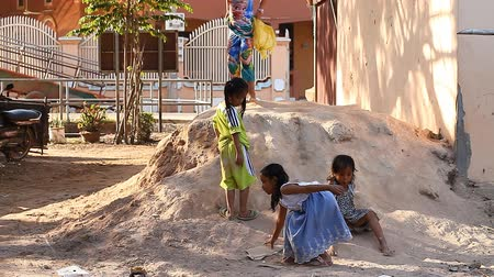 ghetto streets : Siam Reap, Cambodia - January 14, 2017: Children living in a poor village ride on cartons and plastic bags with a clay slide. Heavy childhood of children living in slums and poor villages of Cambodia Stock Footage