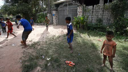 vila : Siam Reap, Cambodia - January 13, 2017: Cambodian children play football on the road in their poor village . Living in poor settlements and slums in Cambodia