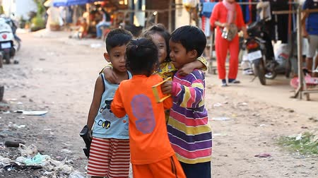 ghetto streets : Siam Reap, Cambodia - January 14, 2017: Three cheerful Cambodian children living in a poor Cambodian village.