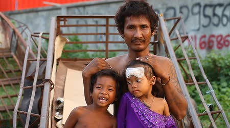 ghetto streets : Siam Reap, Cambodia - January 14, 2017: A homeless drug addict lives with his young children in a spontaneous house of boxes and construction debris.
