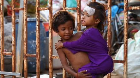sklízet : Siam Reap, Cambodia - January 14, 2017: A homeless boy with his young sister living in a house from empty boxes and construction debris.