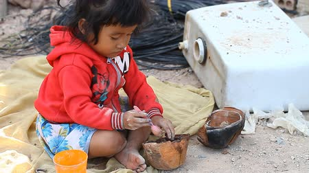 ghetto streets : Siam Reap, Cambodia - January 14, 2017: A small Cambodian girl plays next to garbage and waste. Life in the slums and poor villages of Cambodia Stock Footage