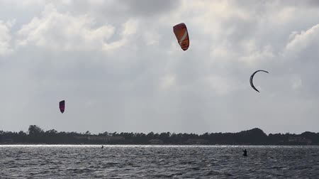 evento : Kitesurfers in action on beach on a cloudy and windy day.
