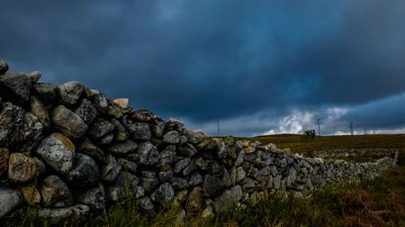 portugalsko : Wall made of rocks on a rural scene with wind turbines on the background. video - time lapse.