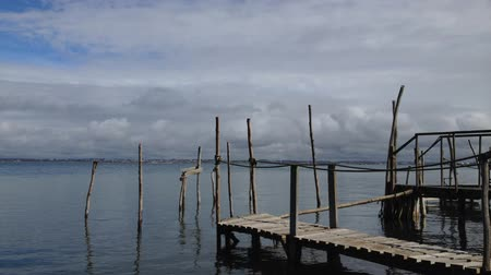 распад : Timelapse of old wood piers, clouds in the sky and water reflections.