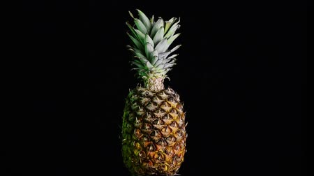 ananas : Big pineapple turning on itself on a black background Stok Video