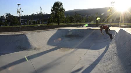 deskorolka : Skateboarder riding a pool on a public skate park.