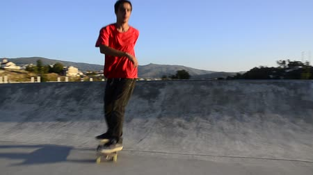 deskorolka : Skateboarder grinding a curb on a ramp at a public skate park. Wideo
