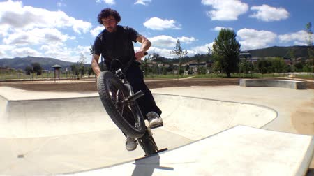 kolo : BMX bike stunts in skateboard park on a sunny day.