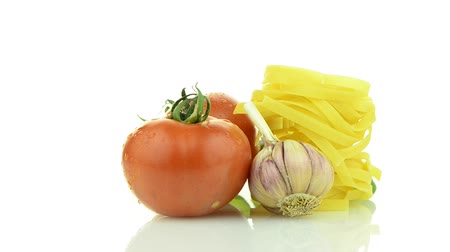 massa : Cherry tomatoes, garlic and pasta rotating Isolated on white background.