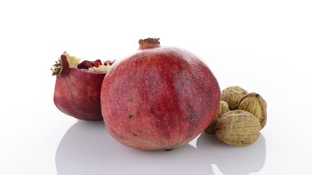 ve slupce : Ripe pomegranate fruit and nuts isolated on white background.