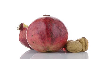 roma : Ripe pomegranate fruit and nuts isolated on white background.
