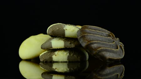 vaj : Closeup detail of delicious butter and chocolate cookies on black reflective background.