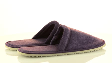 footgear : A pair of purple slippers on a white background.