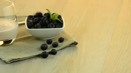 йогурт : Yogurt and blueberries set on a wooden table.