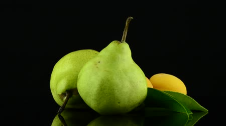 pivoting : Apricots and pears rotating on black reflective background. Stock Footage