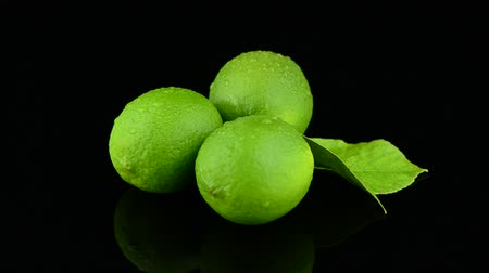 pivoting : Fresh green limes rotating on black reflective background.