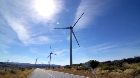 moinho de vento : Rotating windmills and paved road. Alternative renewable energy generation.