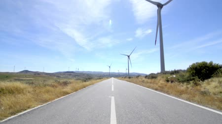 türbin : Rotating windmills and paved road. Alternative renewable energy generation.