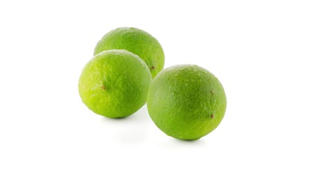 calcário : Fresh green limes isolated on white background, slide from back left to right front.