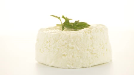 sýr : Cottage cheese with parsley leaf rotating on white background.