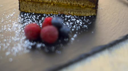 arduvaz : Piece of chocolate cake with berries on dark slate tray.