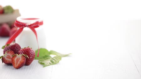 йогурт : Strawberries and yoghurt dessert on white wooden table.