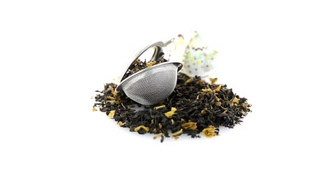 hibiscus tea : Aromatic black dry tea with petals and a tea strainer on white reflective background.