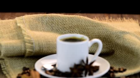 saborear : Coffee cup with burlap sack of roasted beans on rustic table