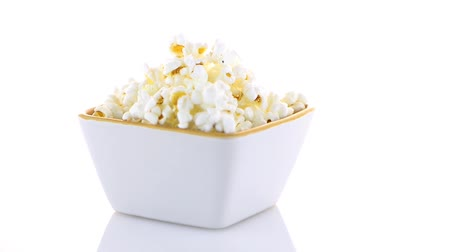 попкорн : Popcorn in a white bowl on a white background Стоковые видеозаписи
