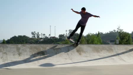 deskorolka : Skateboarder  performing a grind trick on a skatepark.