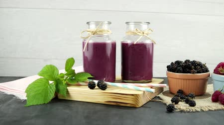 йогурт : Fresh red fruits smoothie on vintage decorated  wooden table. Стоковые видеозаписи