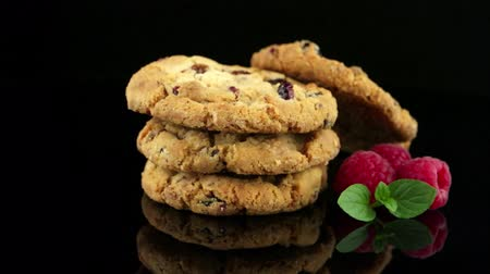 keksz : Dried fruits chip cookies and raspberries isolated on black background.