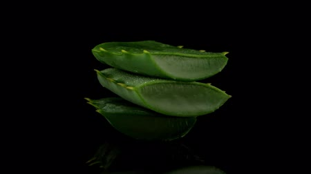 pleťová voda : Sliced aloe leaf and water drops isolated on black background.
