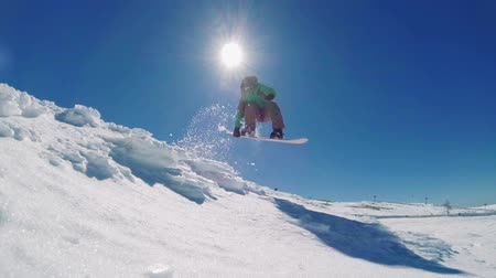 esqui : Snowboarder executing a radical jump against blue sky.