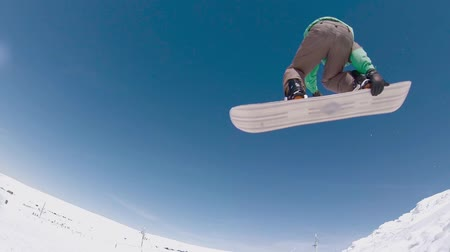 snowboard : Snowboarder executing a radical jump against blue sky.