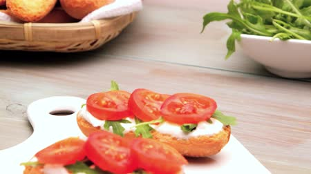 ocet : Bruschetta with cottage cheese, tomatoes and arugula served on white creamic tray.