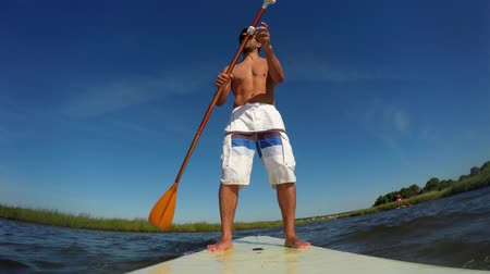 стоять : Man stand up paddleboarding on lake. Young man doing watersport on lake. Male tourist in swimwear during summer vacation.