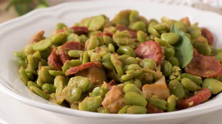 laur : Boiled broad bean with chorizo and laurel leaves on a white ceramic plate. Typical portuguese food.