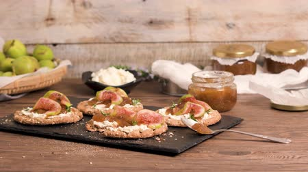 crostini : Canape or crostini with multigrain  crispread with cream cheese and fig jam on a slate board. Delicious appetizer ideal as an aperitif.