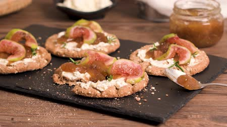 bruschetta : Canape or crostini with multigrain  crispread with cream cheese and fig jam on a slate board. Delicious appetizer ideal as an aperitif.