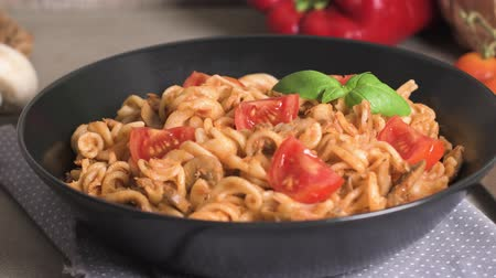 italian speciality : Italian Pasta with Tuna and Basil. Fresh pasta with tuna and tomato sauce on old wooden background. Stock Footage