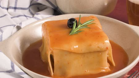 villa : Traditional Portuguese snack food. Francesinha sandwich of bread, cheese, pork, ham, sausages, with tomato beer sauce and French fries. With beer and potatoes. On table.