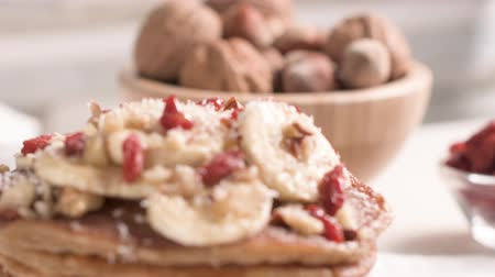 orzech : Healthy breakfast table,  homemade pancakes with banana, goji and walnuts.