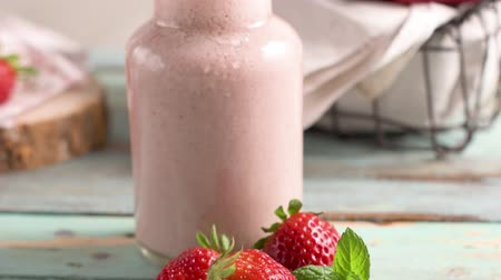 harmanlanmış : Healthy strawberry smoothie in a mason glass jar with scattered fruits over a rustic wood background Stok Video