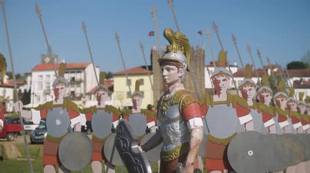 lima : PONTE DE LIMA, PORTUGAL - CIRCA APRIL 2018: Statues of roman soldiers near Lima River at Ponte de Lima with Medieval Tower of the Old Jail on the background. These statues were created by Salvador Viera and Mario Rocha in 2009. Stock Footage